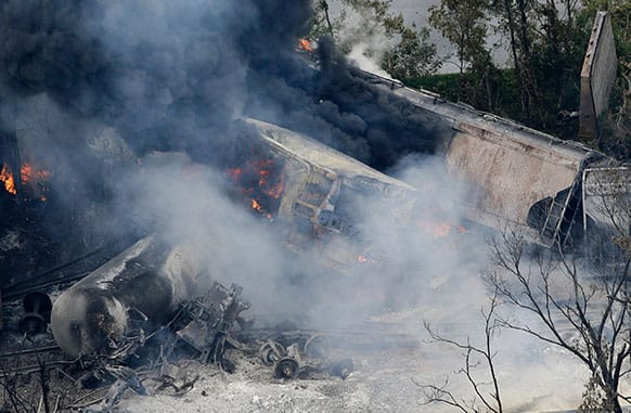 A fire burns at the site of a CSX freight train derailment in Rosedale, Md., where fire officials say the train crashed into a trash truck, causing an explosion that rattled homes at least a half-mile away and collapsed nearby buildings, setting them on fire.