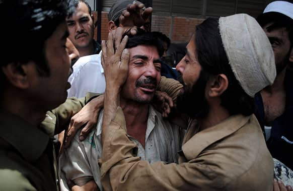 People comfort a family member of a female polio worker who was killed by unknown gunmen, at a local hospital in Peshawar, Pakistan.