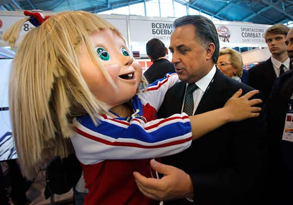 Russia`s Sports Minister Vitaly Mutko embraces a Masha mascot of 2013 Combat Games at the SportAccord International Convention in St.Petersburg, Russia.