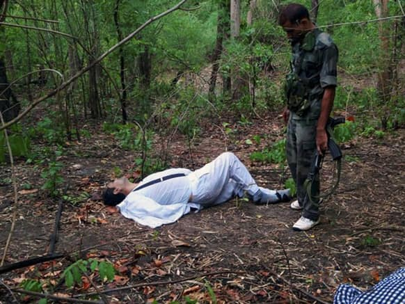 An Indian security person stands near the body of one of the victims of Saturday's Maoist attack in a densely forested area in Bastar, about 345 kilometers (215 miles) south of Raipur, Chhattisgarh.