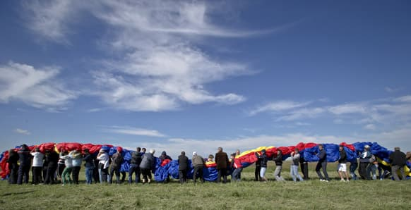 Romanians carry a huge national flag on the Clinceni Airfield, south of Bucharest, Romania. Romania entered the Guinness Book of records after it unveiled the largest flag ever made.