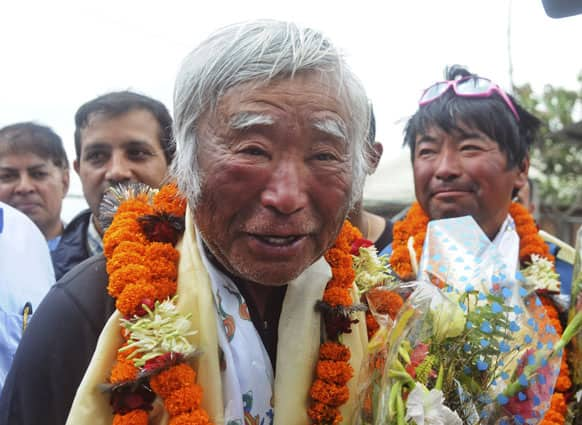 80-year-old Japanese climber Yuichiro Miura, who became the oldest conqueror of Mount Everest on Thursday, is garlanded as he returns from camp 2 by helicopter in Katmandu.