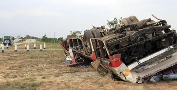 A damaged bus lies beside the high way road in Phyu, Myanmar.
