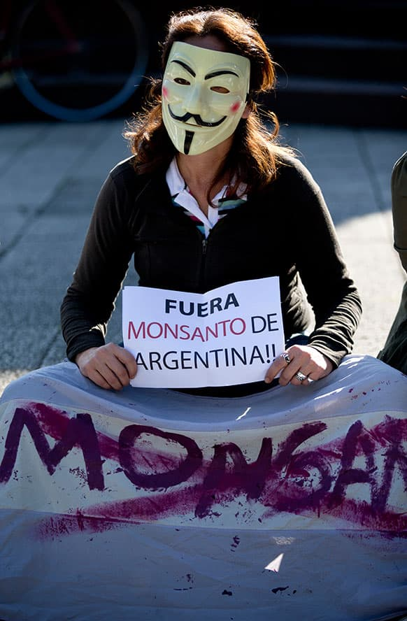 A demonstrator wearing as Guy Fawkes mask holds a sign that reads in Spanish