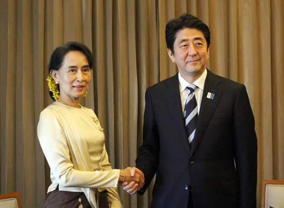 Myanmar Opposition Leader Aung San Suu Kyi, left, and Japanese Prime Minister Shinzo Abe, right, pose for photos before their meeting at a hotel in Yangon, Myanmar.