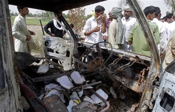 Pakistanis gather by the wreckage of a minibus, which was burnt after gas cylinder explosion, in Gujrat, Pakistan. Police say that a teacher was among more than a dozen people burned to death in eastern Pakistan when a minibus taking children to school suddenly caught fire.