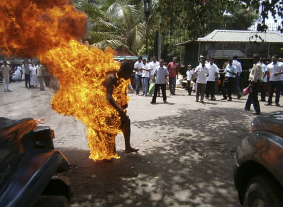 A Sri Lankan Buddhist monk identified as Bowatte Indrarathane walks after self immolating outside the sacred Temple of the Tooth in Kandy, Sri Lanka. Indrarathane allegedly set himself on fire during a protest demanding an end to cattle slaughter, according to Press Trust of India.