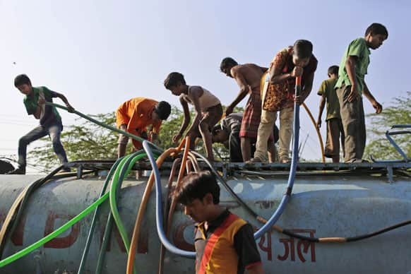 An Indian girl sucks on a hose to pull water as she stand on top of a government tanker delivering drinking water because of short supply in running water taps at a slum in New Delhi.