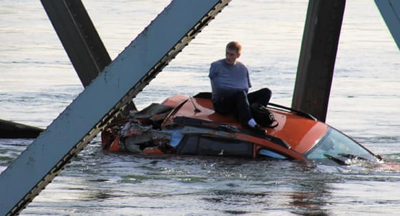 This photo provided by Francisco Rodriguez, a man is seen sitting atop a car that fell into the Skagit River after the collapse of the Interstate 5 bridge, in Mount Vernon, Wash.