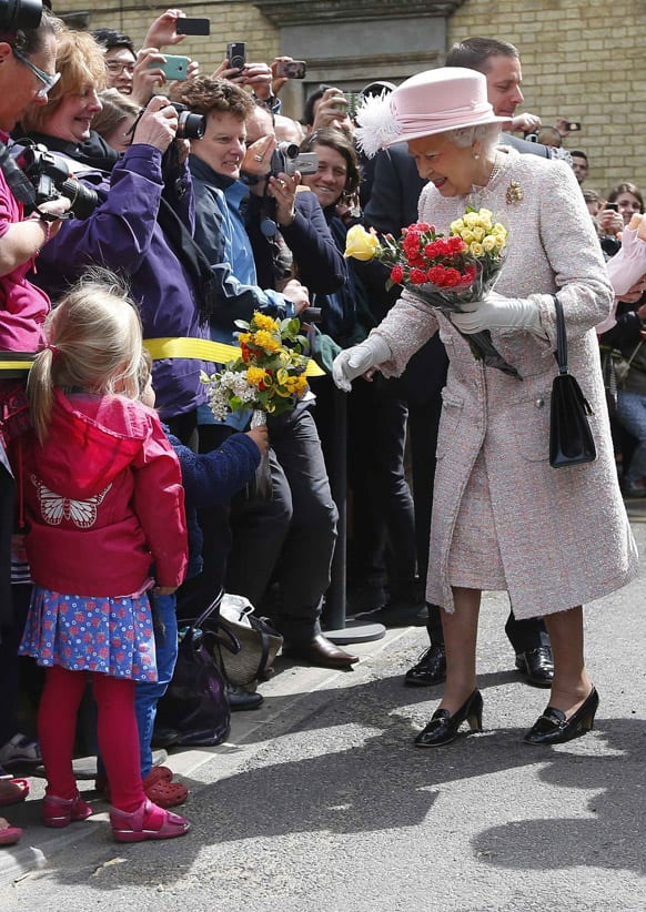 Britain`s Queen Elizabeth II receives bouquets of flowers from children as she is welcomed during a visit to Cambridge, England.