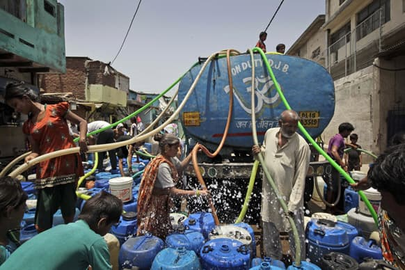 People fill water, supplied by a government tanker, into barrels in New Delhi. Many areas of the Indian capital are facing acute water shortage, a repeated annual phenomenon during summer when taps go dry as demand rises.