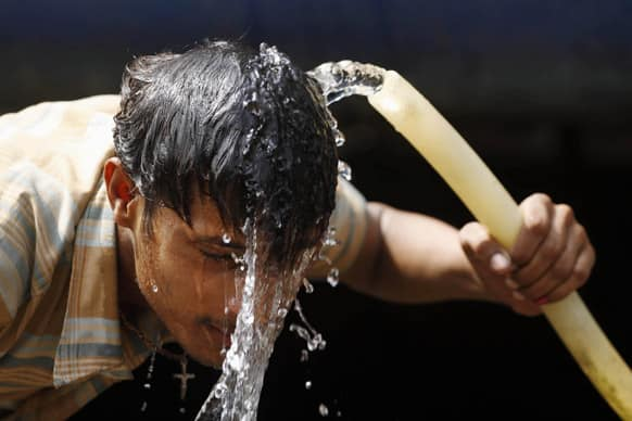 A commuter splashes water from a pipe onto his face to get respite from the heat at the railway station in Allahabad. Most of north India has been reeling under heat wave conditions with the mercury soaring to over 46 degree Celsius.