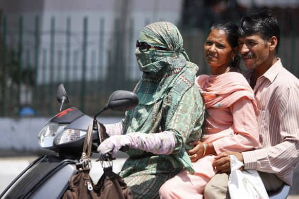 A couple rides pillion behind a woman with her face covered to protect herself from the heat, in Jammu.
