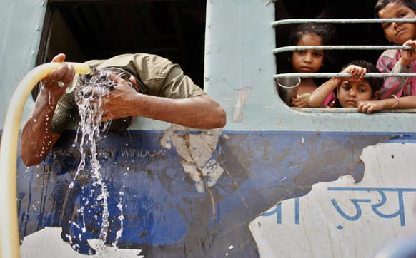 A commuter pours water over his head to cool off as young children watch from a window at a railway station in Allahabad. Most of north India has been reeling under heat wave conditions with temperature soaring to over 46 degree Celsius.