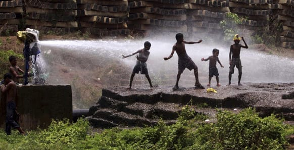 Slum children play in water sprinkling out of a water supply pipeline to beat the heat in a hot afternoon in the eastern Indian city of Bhubaneswar.
