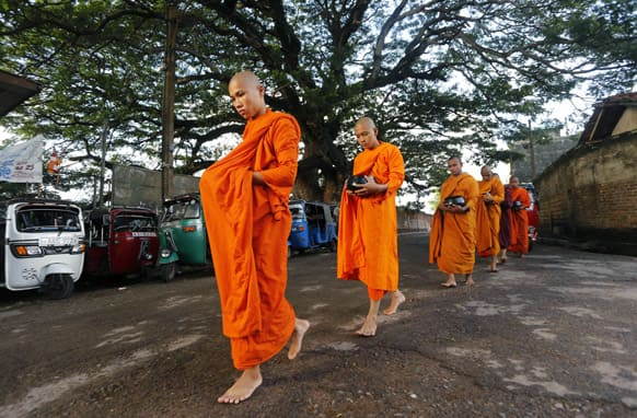 Bangladeshi Buddhists monks living in Sri Lanka parade through a street seeking alms on the eve of Vesak or Buddha Poornima in Colombo, Sri Lanka. The festival marks Buddha`s birth, enlightenment and death.