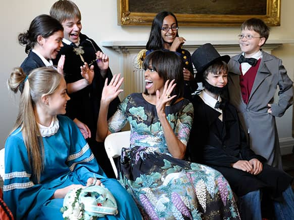 First lady Michelle Obama reacts as she surprises schoolchildren from Willow Springs Elementary School in Fairfax, Va., before they performed part of a play at the Decatur House, in Washington.