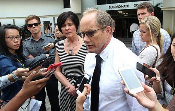 The parents of late American software engineer Shane Truman Todd, Mary, center left, and Rick Todd, right, with their son Dylann, second left, watching as they speak to reporters after leaving the Subordinate Courts of Singapore.