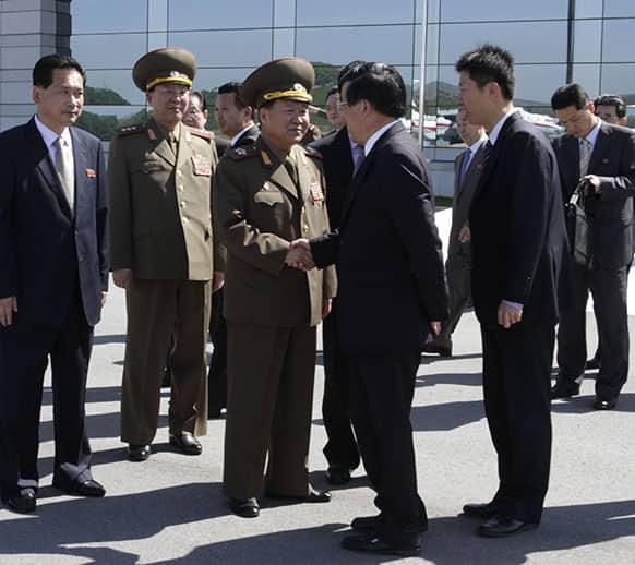 High-ranking North Korean party and military official Choe Ryong Hae, center left, shakes hands with Chinese Ambassador Liu Hongcai as Choe departs for China as a special envoy of North Korean leader Kim Jong Un, at Pyongyang airport, North Korea.