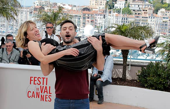 Actor Filippo Timi carries director Valeria Bruni Tedeschi as they pose during a photo call for the film Un Chateau en Italie at the 66th international film festival, in Cannes.
