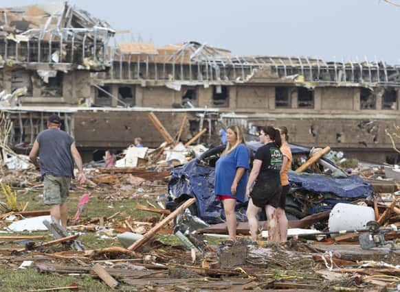 People go through the debris near Telephone Road and SW 4th Street after a tornado moves through Moore, Okla.