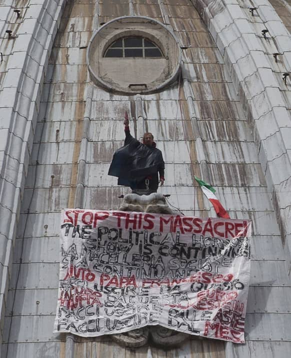 Italian businessman Marcello di Finizio stands by his banner with writings against the Italian Government and the Euro as he protests on St. Peter`s 130-meter-high (42-feet-high) dome, at the Vatican.