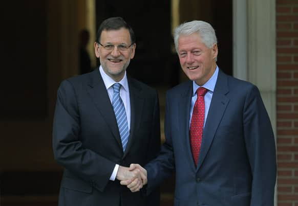 Spain`s Prime Minister Mariano Rajoy, shakes hands with former US President Bill Clinton during a meeting at the Moncloa Palace, in Madrid.
