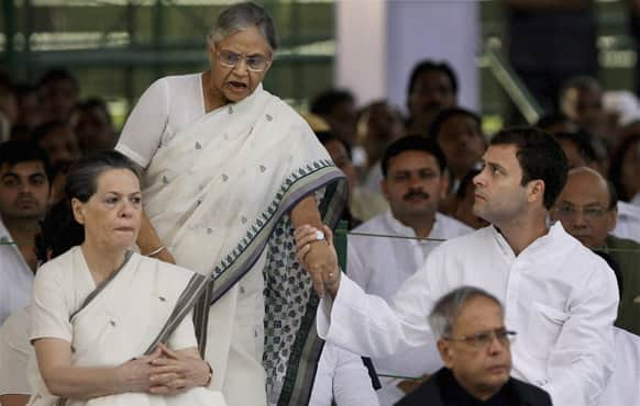 Congress party leader Rahul Gandhi, holds the hand of Delhi Chief Minister Sheila Dixit at a prayer meeting to mark the death anniversary of his father and former Indian Prime Minister Rajiv Gandhi at his memorial in New Delhi.