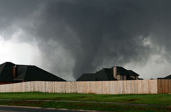 A tornado moves past homes in Moore, Okla.