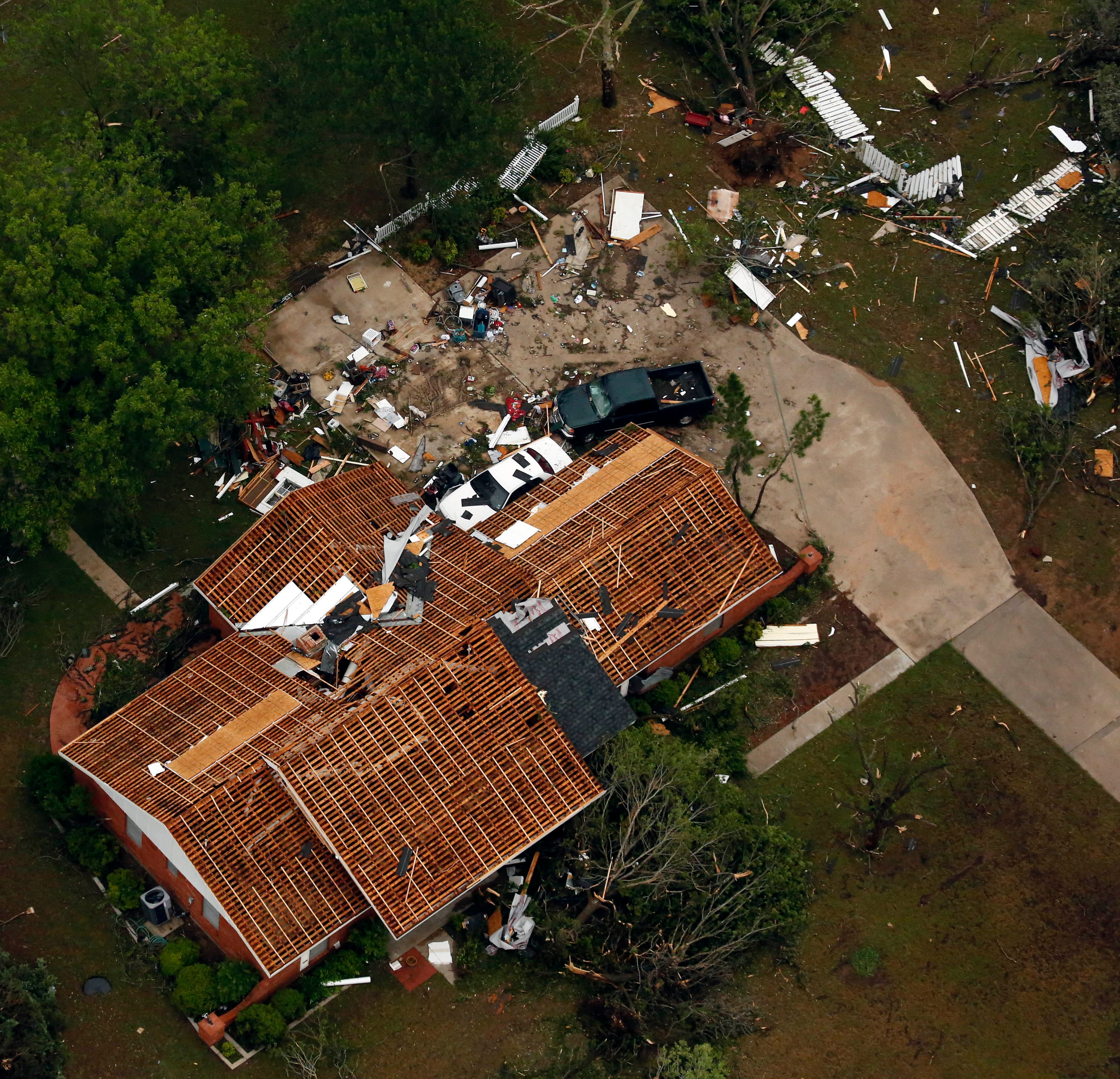 This aerial photo shows a home missing roofing and surrounded by debris in Cleburne, Texas.