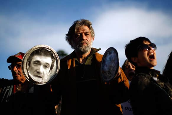 A man bangs pot lids, one of them with the photograph of the Portuguese Prime Minister Pedro Passos Coelho, as others shout slogans during a protest outside Lisbon`s Belem presidential palace where a meeting of the State Council is taking place.