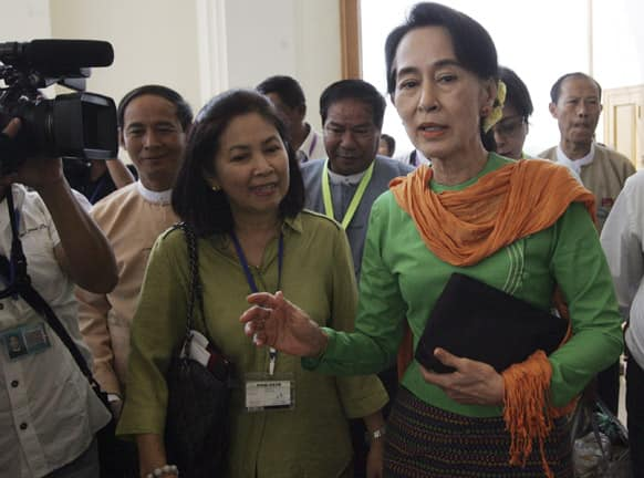 Myanmar Opposition Leader Aung San Suu Kyi, center, talks to journalists as she attends a session of Union Parliament at the Parliament building in Naypyitaw, Myanmar.