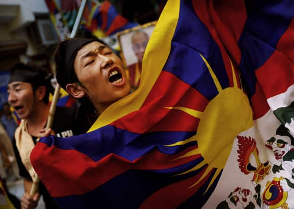 An exiled Tibetan holds a Tibetan flag as he shouts slogans during a protest at a local neighborhood after they were stopped from protesting near the venue where Chinese Premier Li Keqiang was attending a meeting, in New Delhi.