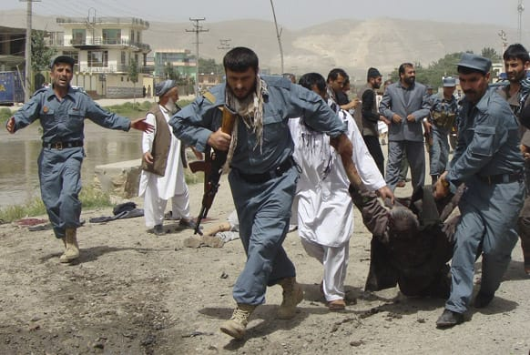 Afghan policemen evacuate a wounded person after a suicide bomber struck outside a provincial council headquarters in Pul-i-Khumri, Baghlan province, northern Afghanistan.