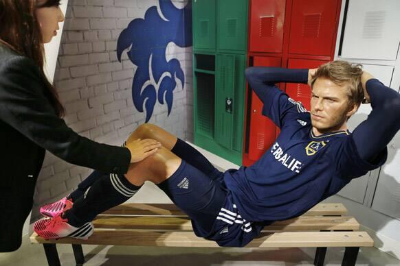 A woman touches a wax figure of soccer superstar David Beckham at the Madame Tussauds Tokyo.