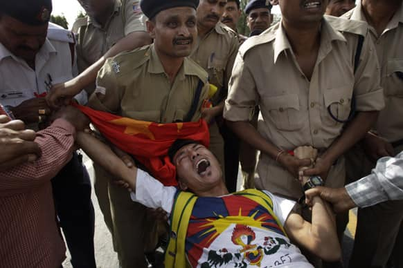 Policemen detain a lone Tibetan protestor who tried to stage a protest against the visit of Chinese Premier Li Keqiang outside the Chinese embassy, in New Delhi.