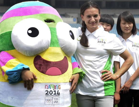 Russian pole vaulter and Olympic gold-medalist Yelena Isinbaeva, right, poses for photos with a mascot of Nanjing 2014 Youth Olympic Games at a stadium in Nanjing, in eastern China`s Jiangsu province.