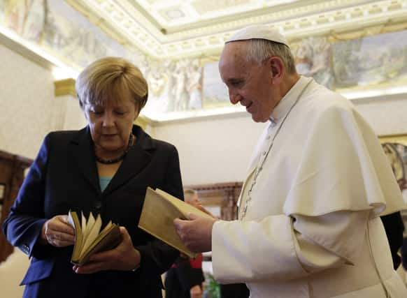 Pope Francis is presented with a gift by German Chancellor Angela Merkel during a private audience at the Vatican.