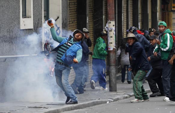 A demonstrator returns a tear gas canister fired by police during a protest by striking miners in La Paz, Bolivia.