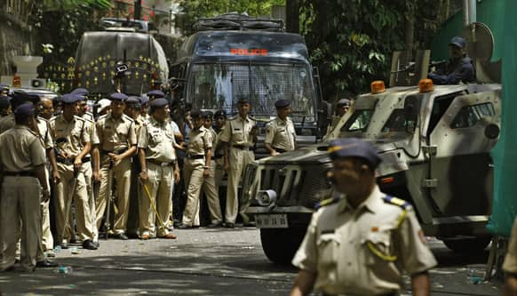 Police officers stand guard outside as Bollywood star Sanjay Dutt, unseen, leaves his home to surrender before a court in Mumbai.
