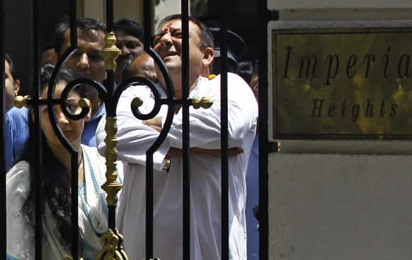 Sanjay Dutt`s wife Manyata watches as the Bollywood star gestures to the media as he leaves his home to surrender before a court in Mumbai.