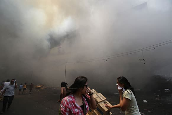 Filipino women cover their noses as they pass by a still burning mall in the shopping district of Divisoria in Manila, Philippines. Authorities are still determining the cause of the fire.