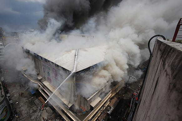 Firemen try to contain the fire at a mall in the shopping district of Divisoria in Manila, Philippines. Authorities are still determining the cause of the fire.