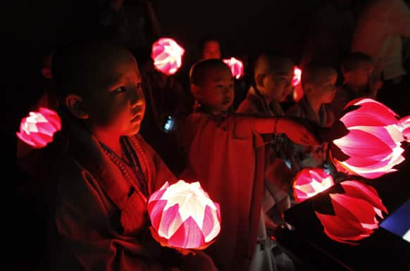 Shaven-headed young boys with lanterns watch a screen at SK Telecom T.um Museum in Seoul, South Korea. The children entered a temple to have an experience of monks` life for three weeks, called Little Buddha Camp, to celebrate upcoming Buddha`s birthday which falls on May 17.