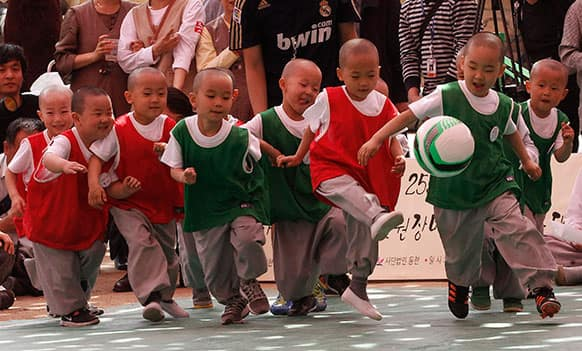 Shaven-headed young boys play the Dongjasung (little monk) soccer match to celebrate Buddha`s upcoming birthday on May 17 at Jogye temple in Seoul, South Korea.