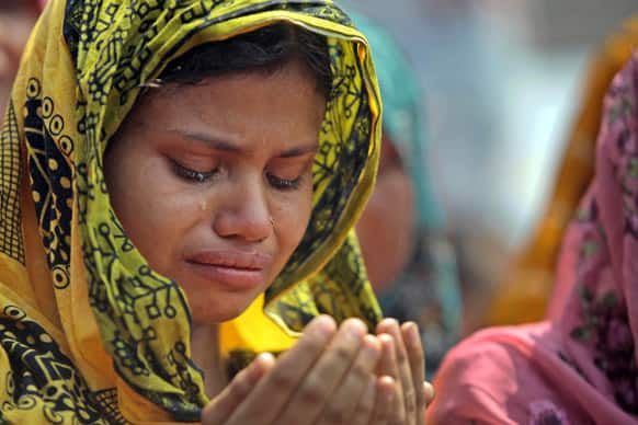 A family member of a victim cries as she offers prayers for the souls of the 1,127 people who died in the garment building structure collapse last month, in Savar, near Bangladesh.