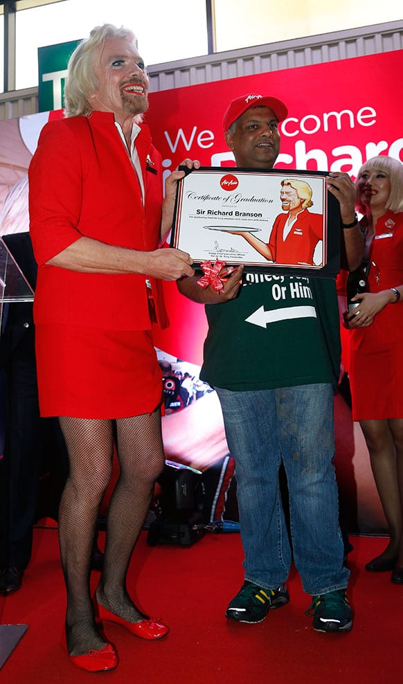 British entrepreneur Richard Branson, left, poses with AirAsia`s Chief Executive Tony Fernandes while dressed as an AirAsia flight attendant at a low cost carrier terminal in Malaysia.