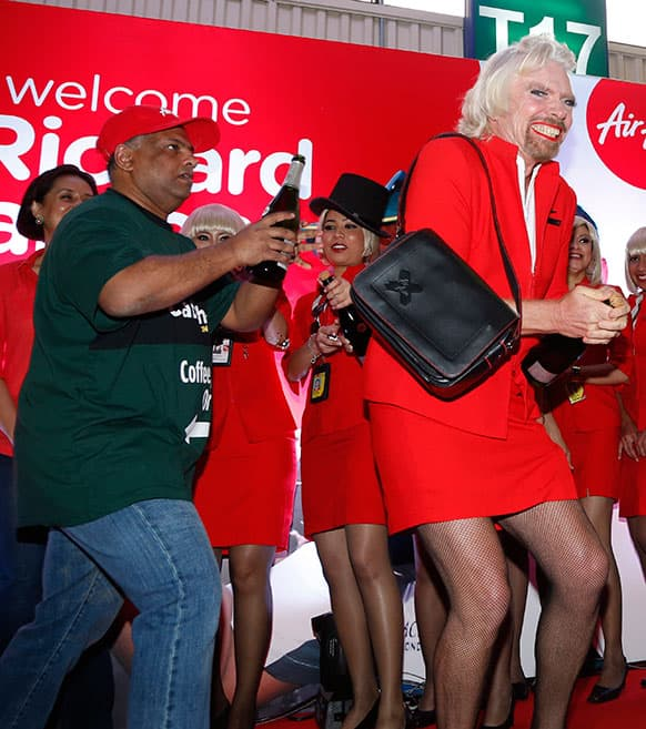 British business magnate Richard Branson, right, dressed up as an AirAsia flight attendant, and AirAsia`s Chief Executive Tony Fernandes prepare to spray champagne during an AirAsia promotional event after Branson arrived at the low cost carrier terminal in Kuala Lumpur, Malaysia.