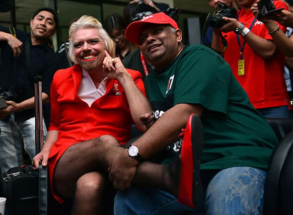 British entrepreneur Richard Branson, left, poses with AirAsia`s Chief Executive Tony Fernandes while dressed up as an AirAsia flight attendant at a low cost carrier terminal in Malaysia.