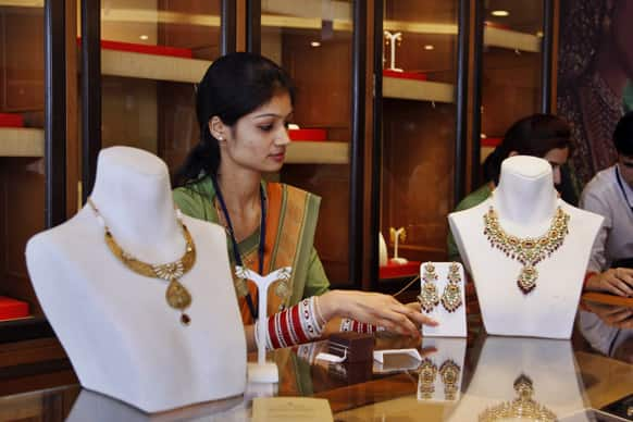 An Indian salesclerk displays gold necklaces at a shop in Jammu.